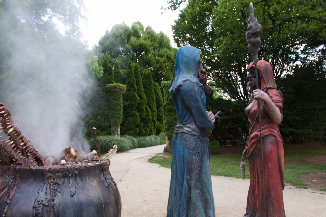 Three witches standing beside a boiling cauldron.