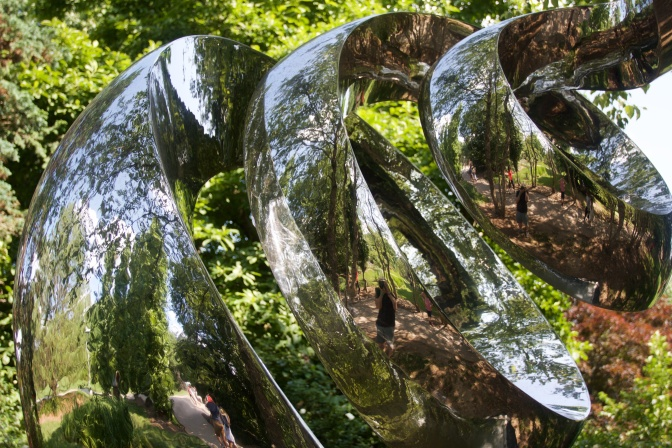 Spiral sculpture, with a reflection of the background.