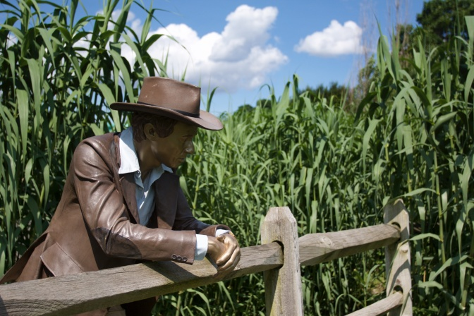 Sculpture of man standing at wooden fence, with corn behind him.