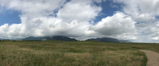 Panorama of foothills of Rocky mountains, with clouds in the sky and a grassy prairie in the foreground.