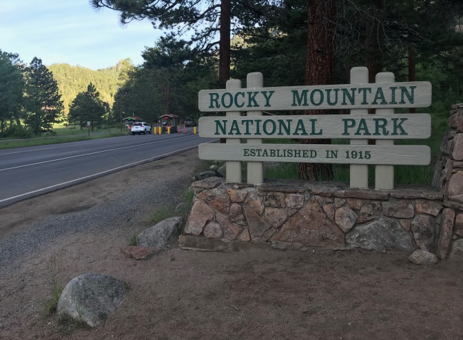 Entrance road to the park, with a large sign in foreground that says ROCKY MOUNTAIN NATIONAL PARK ESTABLISHED IN 1915.