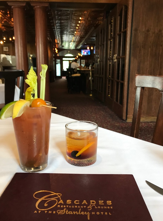 Bloody Mary and Old Fashioned in front of menu for Cascades Restaurant and Bar. The hotel bar is in the background.