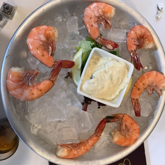 Metal bowl with chilled shrimp on ice, with aioli sauce in white bowl in middle of dish.