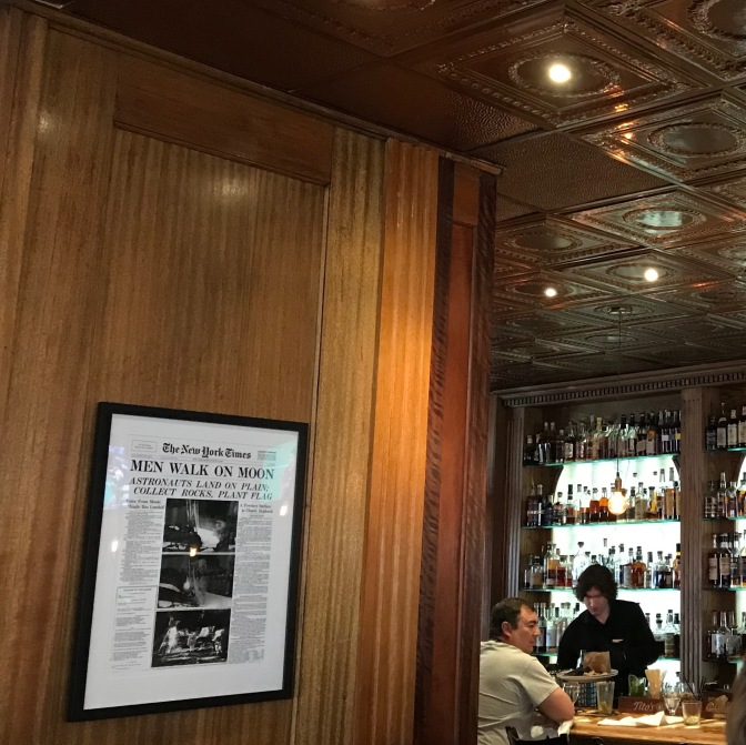 Replica of New York Times with front-page stating MEN WALK ON MOON, hanging on wall in frame. The restaurant bar is in background.