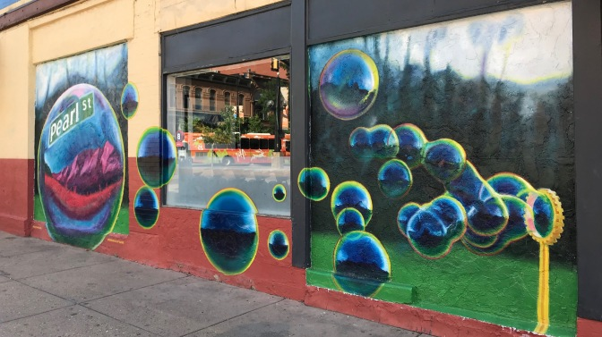 Wall mural of bubbles blowing from right to left. Leftmost bubble says PEARL STREET.