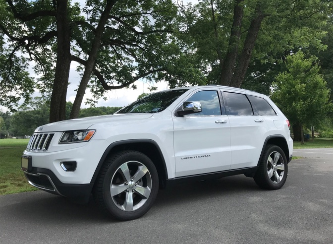 2014 Jeep Grand Cherokee, in white, parked in a park.
