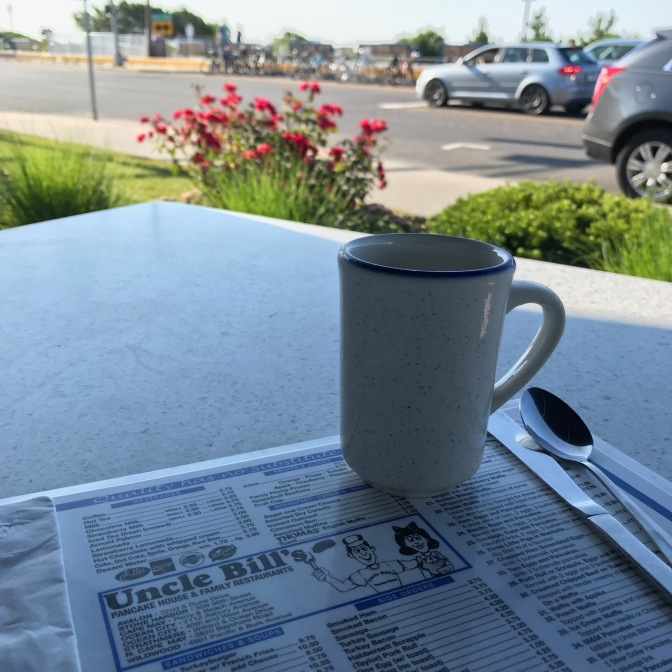 Coffee cup and menu for Uncle Bill's with Ocean Drive in Cape May in the background.