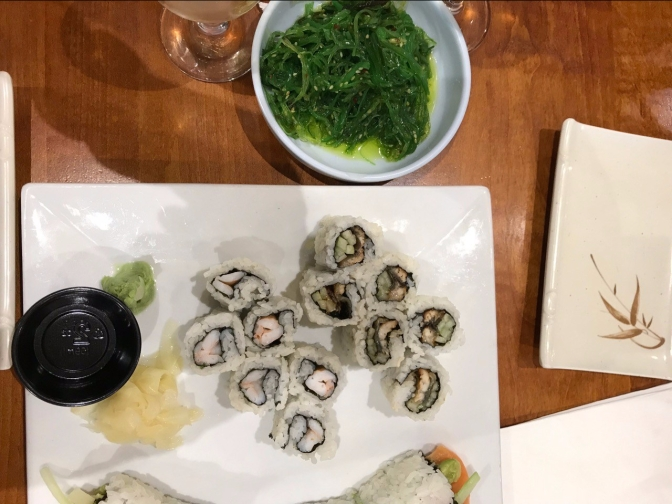 Sushi on square white plate, with seaweed salad in white bowl beside it.
