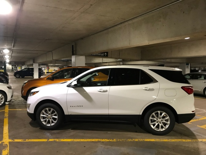 White Chevrolet Equinox parked in parking garage.