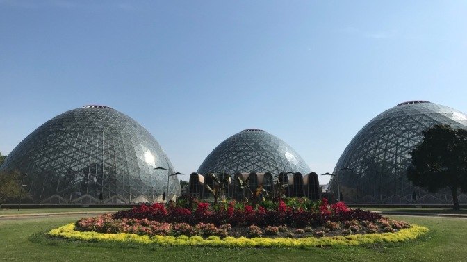 Three of the domes of Mitchell Park Conservatory with flowers and plants in the foreground.