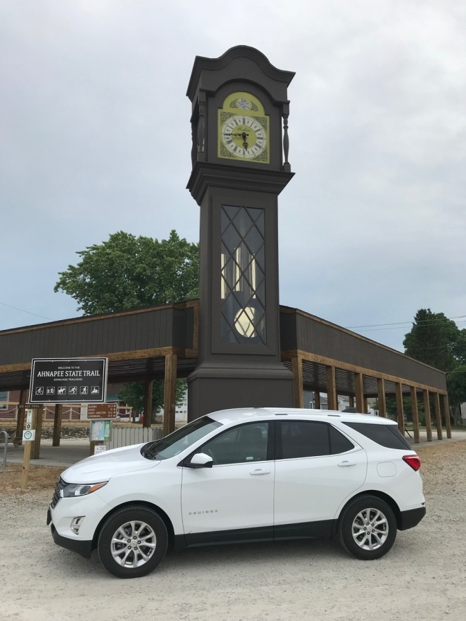 World's Tallest Grandfather Clock with Chevrolet Equinox in foreground.