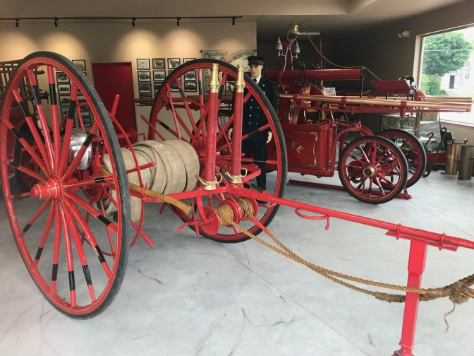 Red cart carrying a hose and an old horse-drawn fire engine.