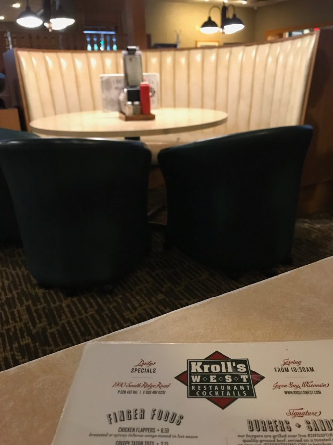 Menu of Kroll's west on table, with empty booth behind it.