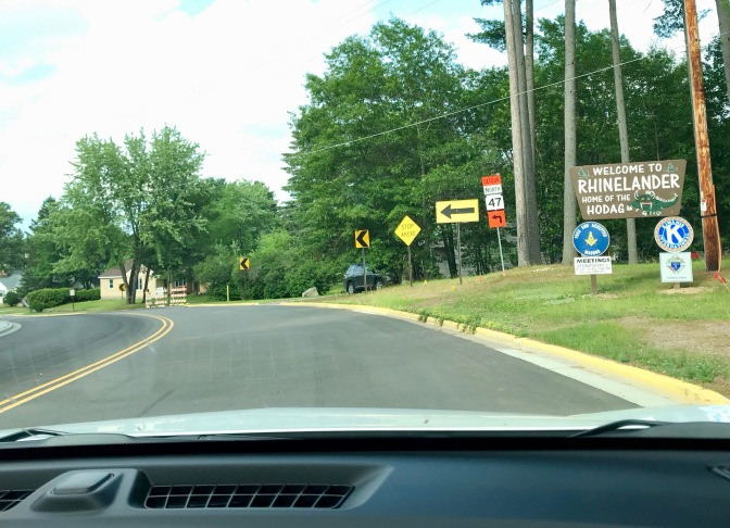 View of street from behind dashboard of car. Sign on right of road says WELCOME TO RHINELANDER HOME OF THE HODAG.