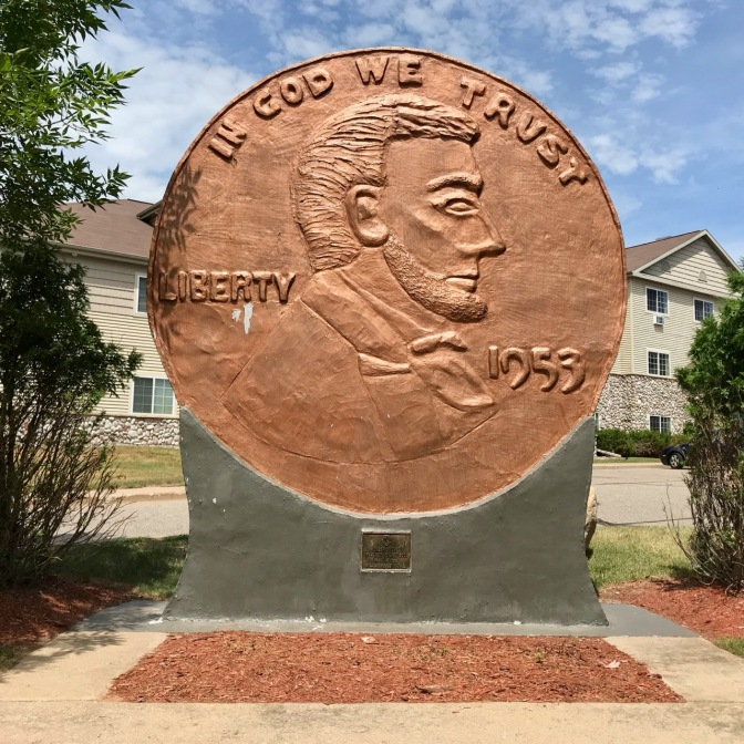 World's Largest Penny, on stand, with building in background. Penny says IN GOD WE TRUST LIBERTY 1953.