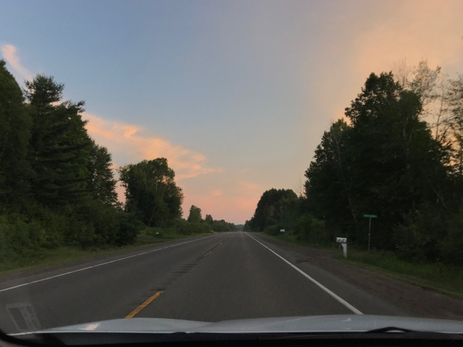 View of sky at dusk through car windshield. A tree-lined road is in the foreground.
