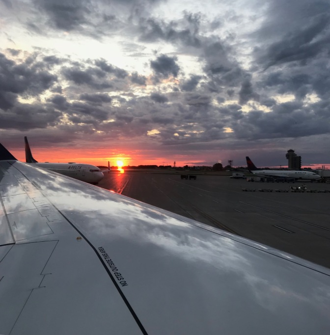 View of sunset over wingtip of airplane parked at airport. Other airplanes are in the background.