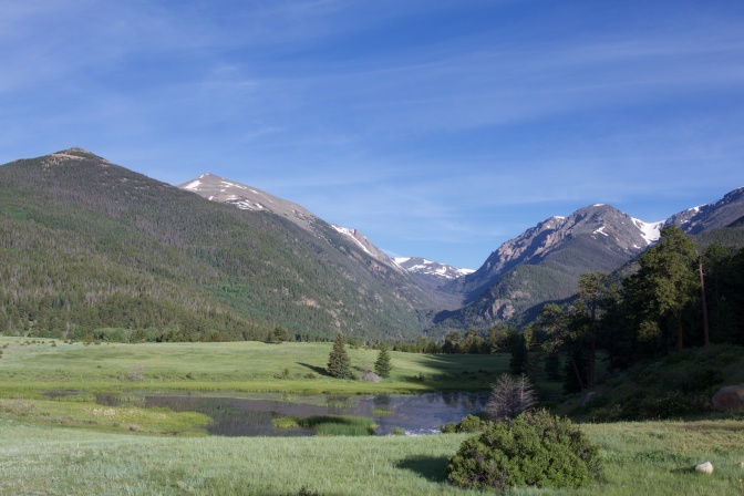 Horseshoe park, with mountains in distance, and a meadow in the foreground.