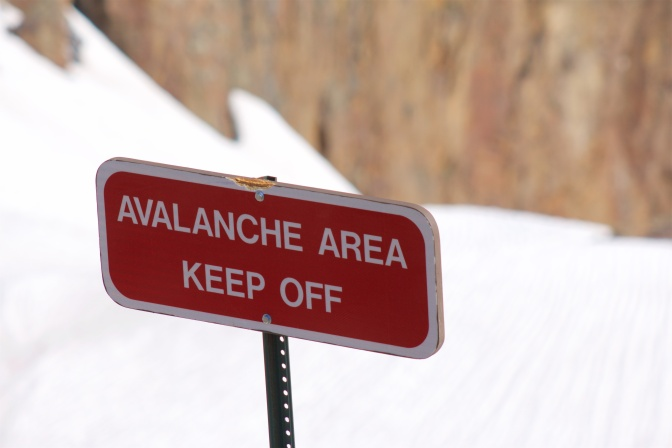 Red sign with white lettering that reads AVALANCHE AREA KEEP OFF