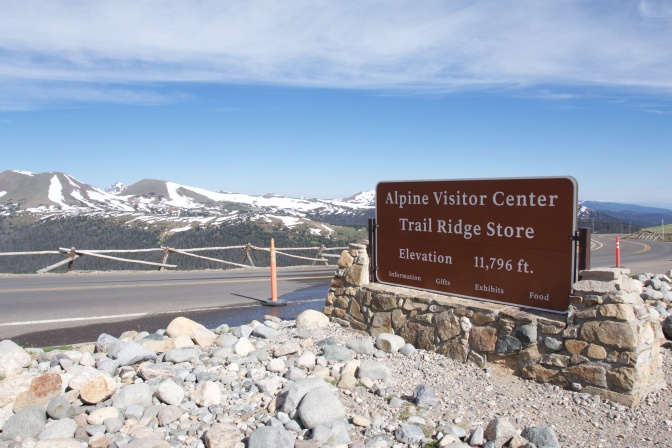 Road with sign that says ALPINE VISITOR CENTER TRAIL RIDGE STORE ELEVATION 11,796