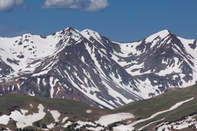 View of mountains, with snow-covered hillsides in foreground.