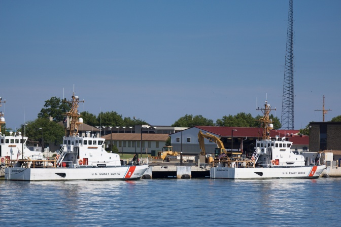Two coast guard vessels tied at pier.