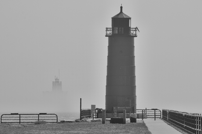 Pierhead Lighthouse in foreground, with Breakwater Light emerging from fog in distance.