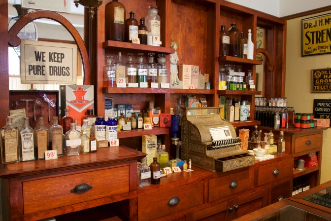 Turn of the century pharmacy counter, with a sign that says WE KEEP PURE DRUGS.