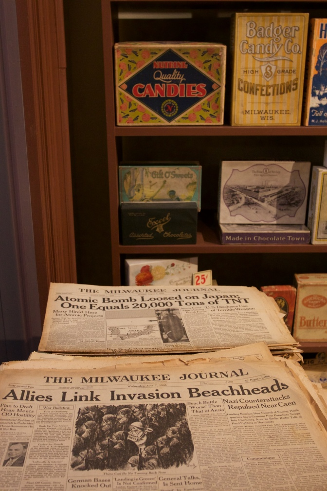 Newsstand with WWII-era newspapers that have headlines for atomic bomb dropped on Japan and allied invasion of France.