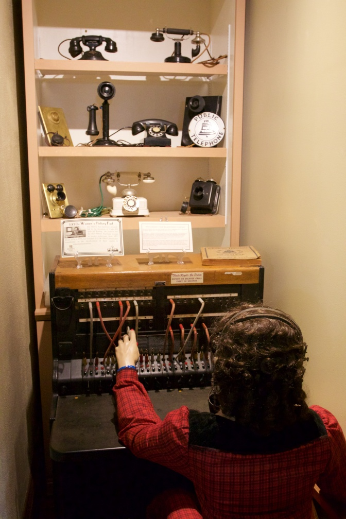 Mannequin at telephone switchboard, with various telephones on shelves above.