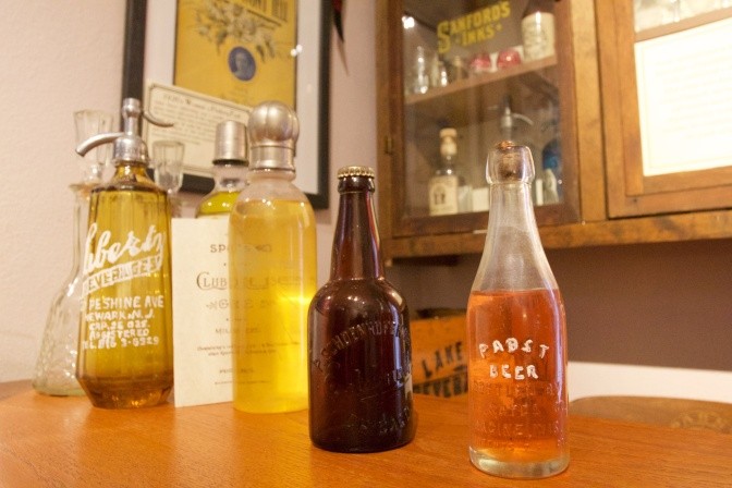Old bottles of alcohol on speakeasy counter.