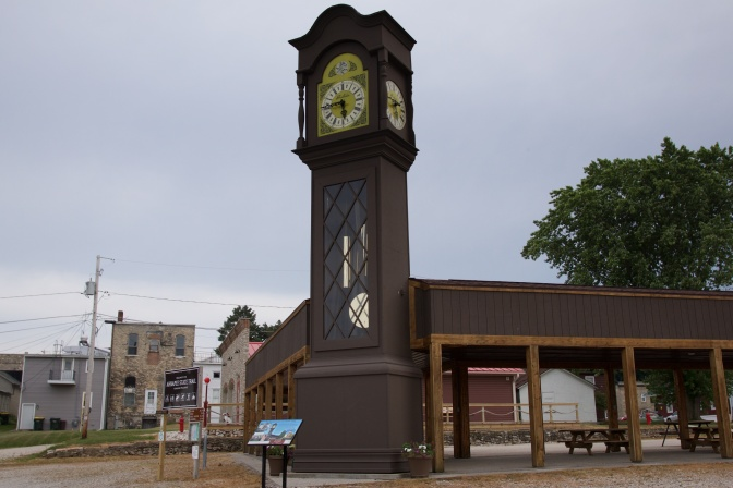 36-foot tall Grandfather Clock, beside a wooden pavilion.