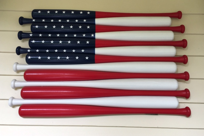 American flag made of baseball bats affixed to wall.