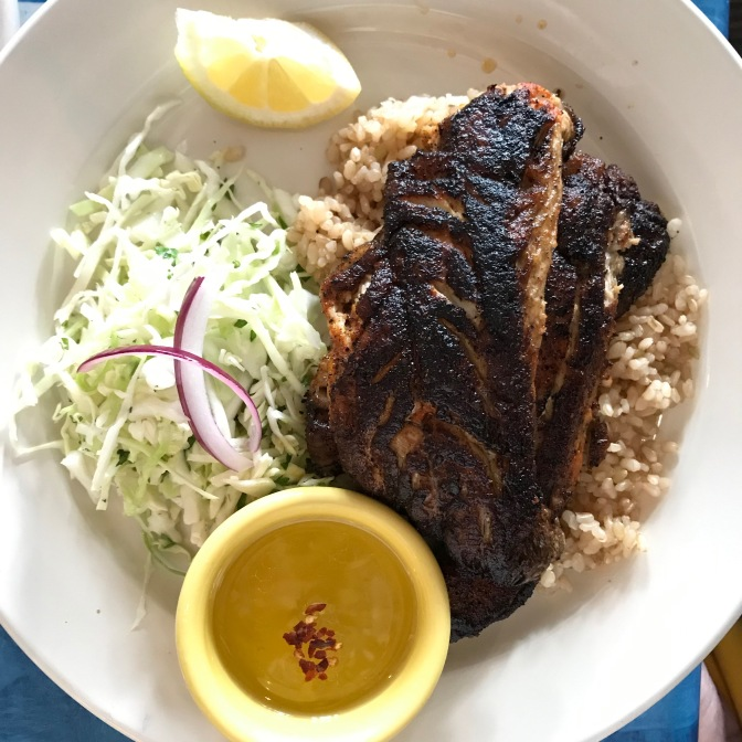 Blackened bluefish with rice and coleslaw on a white plate with a slice of lemon.