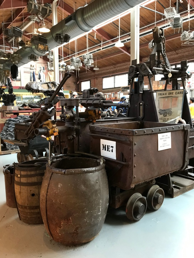 Mining equipment including barrels and mine carts, in museum.
