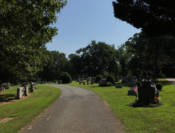 Road in cemetery, with tombstone on either side.