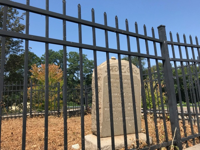 Tombstone behind iron fence.
