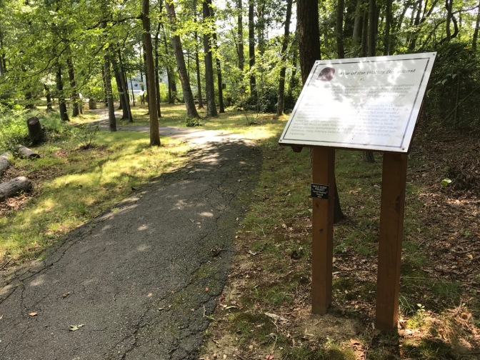 Sign beside path in woods.