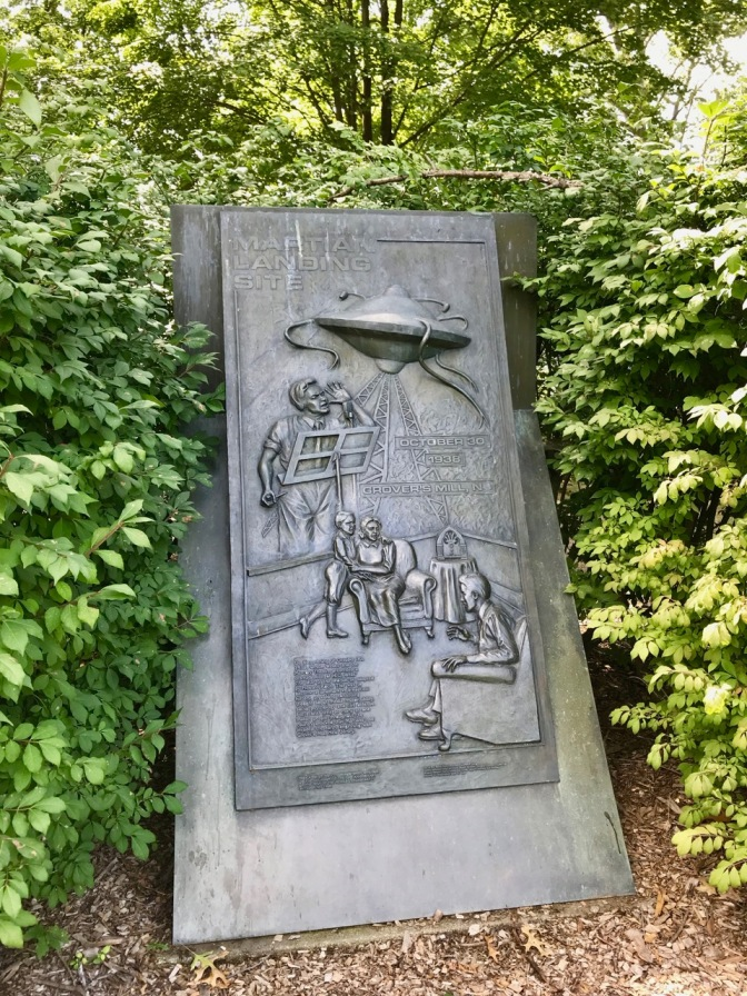 Bas relief plaque depicting Martian invasion, Orson Welles, and listeners at home.