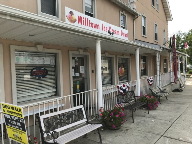 Exterior of Milltown Ice Cream Depot building, with fences and benches in front of building.
