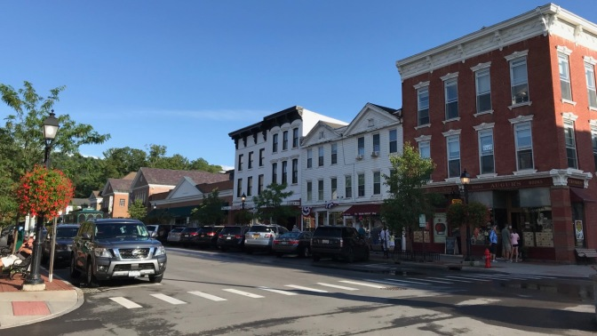 Main Street in Cooperstown with brick and wooden buildings across the street.
