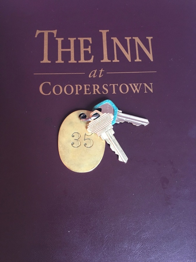 Metal keys on brass tag in front of paper that says THE INN AT COOPERSTOWN.