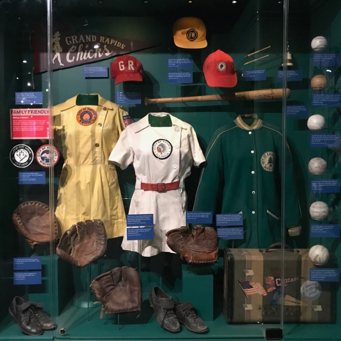 Display of women in baseball, including informs, caps, balls, and bats.