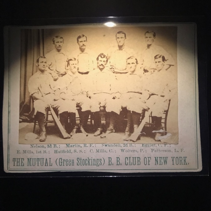 1871 baseball card with 9 players on it and words saying THE MUTUAL GREEN STOCKINGS B.B. CLUB OF NEW YORK.