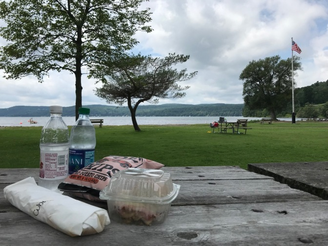 Two bottles of water, two sandwiches, and a bag of chips on a picnic table beside a lake.