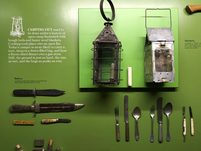 Camping equipment including cutlery, lanterns, and knives.