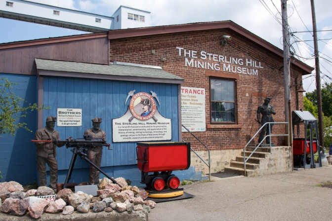 Exterior of visitor center, with statues of miners, a mining cart, and lettering on building that says THE STERLING HILL MINING MUSEUM.