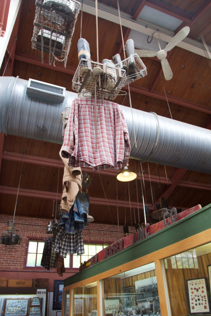Metal baskets hanging from ceiling, with boots and tools inside the baskets and clothes hanging below.