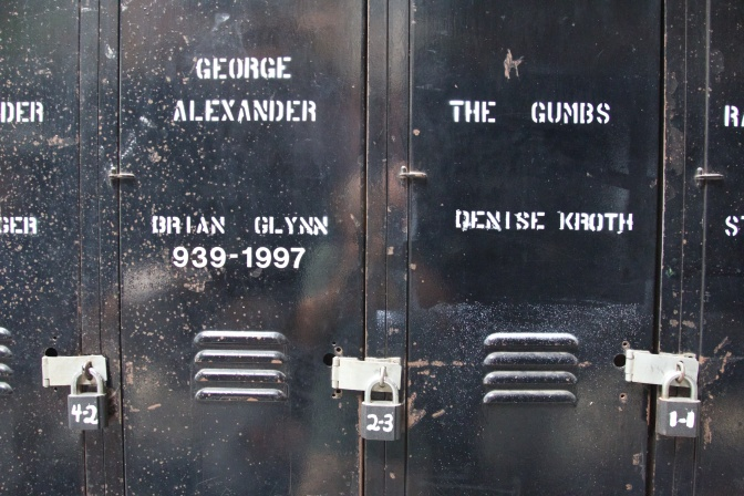 Black lockers with padlocks. Names written on lockers include GEORGE ALEXANDER THE GUMBS DENISE KROTH BRIAN GLYNN