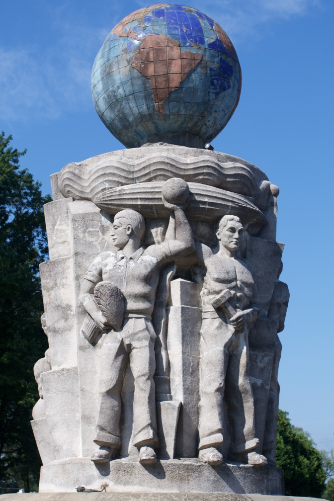 Sculpture of two men working, while a zeppelin floats above them. The Earth is at the top of the sculpture.
